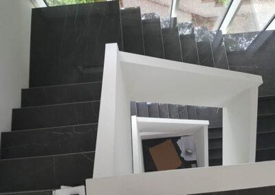 Verlegen von grossformatigen fliesen schwarz auf einer treppe